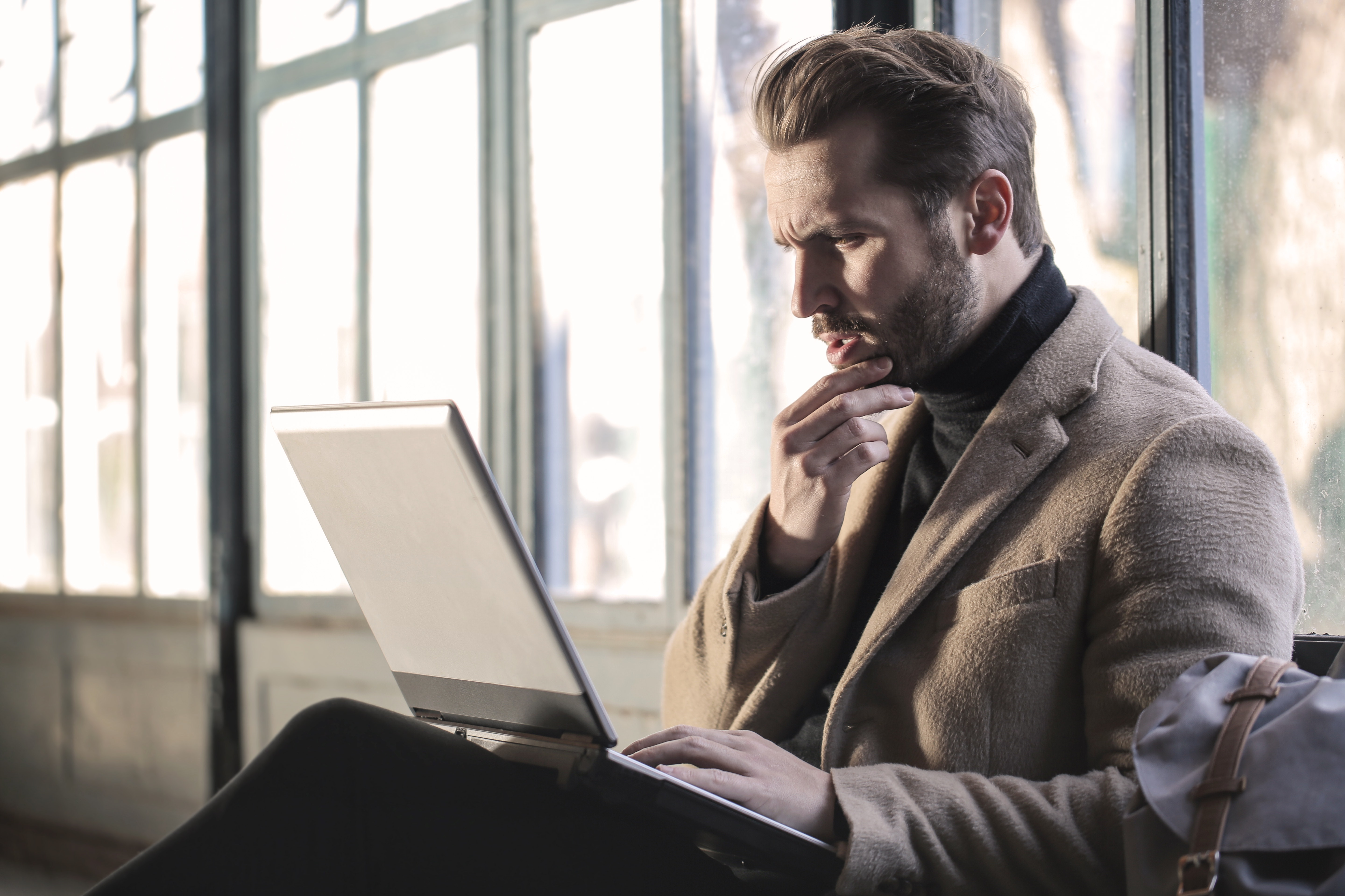 Bearded person looking at a laptop screen confused.