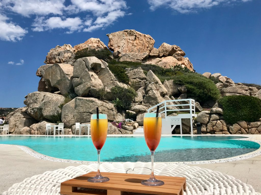 Two cocktails on a table beside a pool.